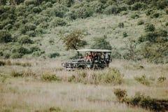 Leute, die weg in Safari auf Straßenfahrzeug reisen stockbild