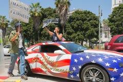 Leute, die Zeichen nahe bei einem Auto gemalt in der Farbe der amerikanischen Flagge halten Stockbild