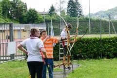 Leute, die zum Bogenschießen bei Massagno auf der Schweiz lernen Lizenzfreie Stockbilder