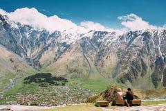 Leute, die zusammen auf einer Steinbank nahe der Gergeti-Dreiheit sitzen Lizenzfreies Stockfoto