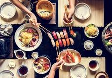 Leute, die zusammen japanisches Lebensmittel essen Stockbilder