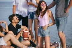 Leute, die zusammen nette Zeit beim Sitzen auf Strand, Haben des Spaßes und Trinken des Bieres verbringen lizenzfreie stockfotografie