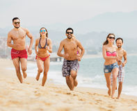 Leute, die zusammen am Ozeanstrand laufen Stockbilder