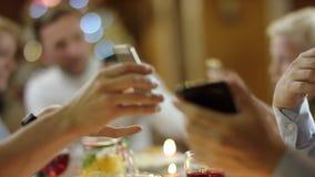 Leute durch die Tabelle, die sich oben ihre Smartphoneschirme in der Heiligen Nacht, Abschluss zeigt stock video footage