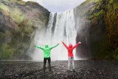 Leute durch Skogafoss-Wasserfall auf Island Stockbild