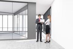 Leute in einem leeren Büro mit den Glas- und weißen Betonmauern Lizenzfreie Stockfotos