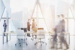 Leute in einem offenen Büro mit dreieckigen Fenstern und Wolkenkratzern Lizenzfreie Stockbilder