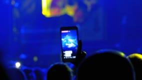 Leute an einem Rockkonzert übertragen direkt auf dem Sozialen Netz unter Verwendung Smartphones stock footage