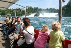 Leute in einem touristischen Boot, das den Rhein-Wasserfällen sich nähert Stockfotos