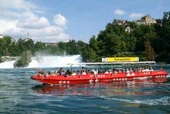 Leute in einem touristischen Boot, das den Rhein-Wasserfällen sich nähert Stockbild