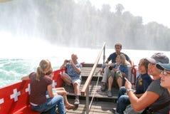 Leute in einem touristischen Boot, das den Rhein-Wasserfällen sich nähert Stockbilder