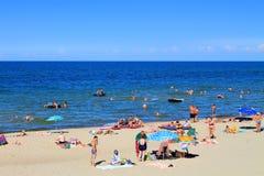 Leute entspannen sich auf dem sandigen Strand der Ostsee im Kulikovo Stockbilder