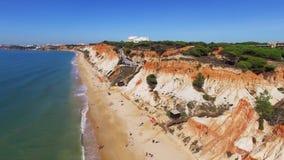 Leute entspannen sich auf dem Strand nahe Ozean unter der Klippen Portugal-Vogelperspektive stock video footage