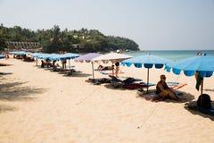 Leute entspannen sich auf den Klubsesseln auf einem Strand Karon Stockbild
