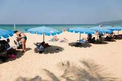 Leute entspannen sich auf den Klubsesseln auf einem Strand Karon Stockfotografie