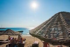 Leute entspannen sich auf den Sonnenruhesesseln unter den Regenschirmen durch das Meer stockfotos