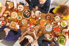 Leute essen gesunde Mahlzeiten an gedientem Tabellenabendessen Stockbild