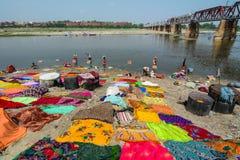 Leute färben traditionelle Kleidung auf Riverbank stockfoto