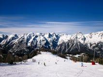 Leute fahren in den Alpen und im schönen Berg im Hintergrund Ski Lizenzfreie Stockfotos