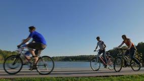 Leute fahren Fahrrad im Stadtpark nahe dem Teich stock video footage