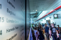 Leute am Flughafen mit Zeitplan Lizenzfreies Stockfoto