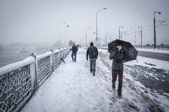 Leute gehen auf die galata Brücke an einem schneebedeckten Tag im Winter Stockbild