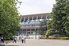 Leute gehen auf ein Quadrat um Baustelle des neuen Nationalstadions in Tokyo lizenzfreie stockfotografie