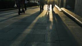 Leute gehen auf gedrängte Straßenpflasterung am sonnigen Abend stock footage