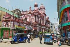 Leute gehen durch die Straße mit Kolonialarchitekturgebäude am Hintergrund in im Stadtzentrum gelegenem Colombo, Sri Lanka Stockbilder