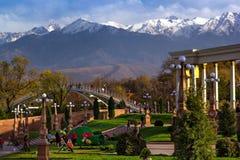 Leute gehen in einen Park mit Ansichten der Berge lizenzfreie stockbilder