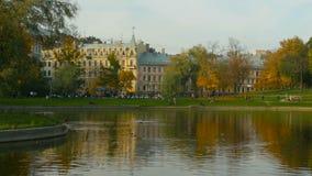 Leute gehen in einen schönen, städtischen Herbstpark stock footage