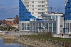 Leute gehen entlang den Damm von Krasnodar nahe den blau-weißen Wolkenkratzern lizenzfreie stockfotografie