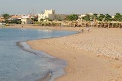 Leute gehen entlang einen verlassenen sandigen Strand durch das Meer in einem tropica Stockbilder
