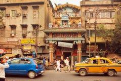 Leute gehen hinter den hindischen Tempel an der Straße mit leistungsfähiger Verkehrsstraße Stockfotografie