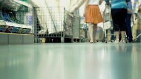 Leute gehen mit Einkaufswagen im Supermarkt stock video footage