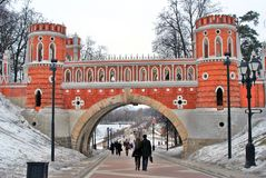 Leute gehen in Richtung zu einer alten Brücke in Tsaritsyno-Park in Moskau Stockfotografie