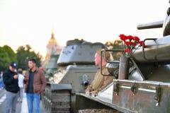 Leute gehen und rote Gartennelken in einer Gewehrpatrone auf der Mitte Lizenzfreies Stockfoto