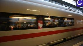 Leute gehen und warten mit dem Zug, der in Anschluss läuft, senden und empfangen Passagiere an Bahnhof Mannheims Hauptbahnhof stock video