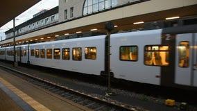 Leute gehen und warten mit dem Zug, der in Anschluss läuft, senden und empfangen Passagiere an Bahnhof Mannheims Hauptbahnhof stock video footage