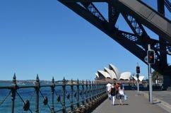 Leute gehen unter Sydney Harbour Bridge in Richtung zu Sydney Opera Ho Lizenzfreie Stockfotografie