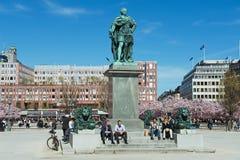 Leute genießen den Mittag, der unter Statue KARLS XII bei Kungstradgarden in Stockholm, Schweden sitzt Stockbild