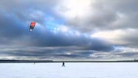 Leute genießen den Wintersport-Drachensnowboarding, der auf einem großen Feld des verschneiten Winters mit Wolken im Himmel snowk stock video footage