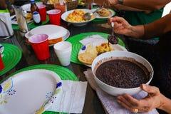 Leute genie?en ein reiches venezolanisches Fr?hst?ck mit arepas, schwarzen Bohnen, Eiern, Wei?k?se, Orangensaft und Kaffee stockfotografie