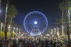Leute genießen, Weihnachtsmarkt mit Riesenrad und Eis zu besuchen Stockfotos
