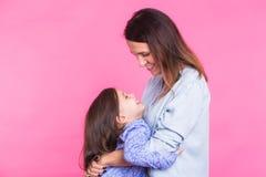 Leute, Glück, Liebe, Familie und Mutterschaftskonzept - glückliche kleine Tochter, die ihre Mutter über Rosa umarmt und küsst lizenzfreies stockbild