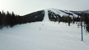 Leute gleiten auf Skis und Snowboards auf dem Berg stock video footage