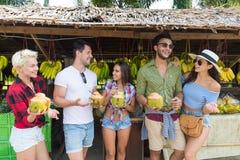Leute-Gruppen-Getränk-Kokosnuss-Cocktail-Asiats-Frucht-Straßenmarkt-, das neues Lebensmittel, junge Freund-Touristen-exotische Fe Stockfotos