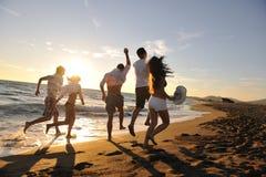 Leute gruppieren Betrieb auf dem Strand Lizenzfreie Stockfotos