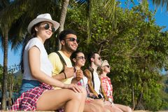 Leute gruppieren das Sitzen unter Palmen im Park auf Strand, zufällige Freund-Abnutzungs-Sonnenbrille-glückliche lächelnde Touris lizenzfreies stockbild