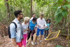 Leute gruppieren mit Rucksack-Trekking auf Forest Path With Giude Using-Zellintelligentem Telefon, Mischungs-Rennjungen Männern u stockfoto
